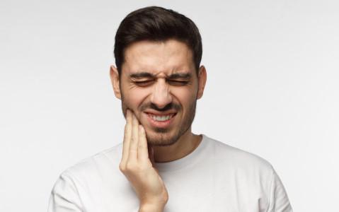 Mann verzieht sein Gesicht schmerzerfüllt - seine Hand liegt am Kiefer